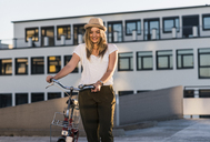 Smiling young woman with bicycle on parking level - UUF12230