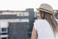 Rear view of smiling young woman wearing a hat - UUF12233