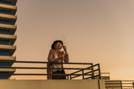 Young woman in the city blowing soap bubbles in the evening - UUF12242