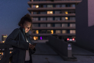 Young woman in the city checking cell phone in the evening - UUF12245
