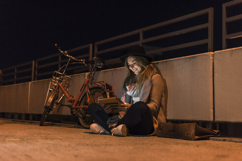 Smiling young woman in the city using tablet at night - UUF12251