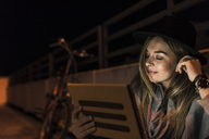 Smiling young woman with tablet and earphones outdoors at night - UUF12254
