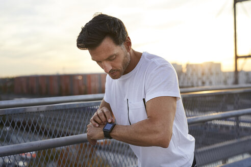 Athlete in the city looking on smartwatch - PNEF00297