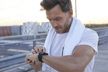 Athlete in the city looking on smartwatch - PNEF00300