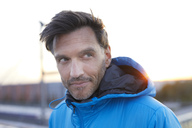 Confident man with hooded jacket in the city - PNEF00303