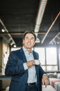 Smiling businessman in office with cup of coffee - JOSF01808