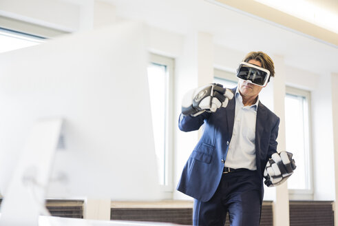 Businessman wearing VR glasses and ice hockey gloves in office - JOSF01814