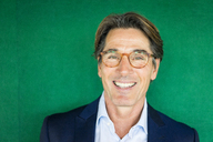 Portrait of smiling businessman with glasses in front of green wall - JOSF01823