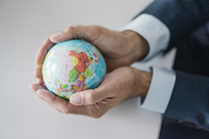 Close-up of hands of businessman holding globe - JOSF01829
