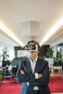 Businessman wearing VR glasses in office - JOSF01835
