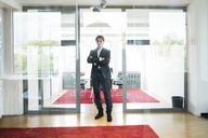 Portrait of confident businessman standing in office - JOSF01841