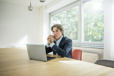 Portrait of businessman with laptop sitting at table in office - JOSF01844