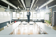 Businessman standing on table in conference room - JOSF01862
