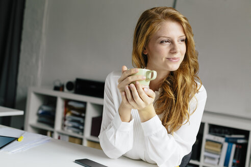 Smiling young woman with cup of coffee at desk in office - BMF00864