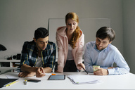 Three colleagues working together at desk in office - BMF00870