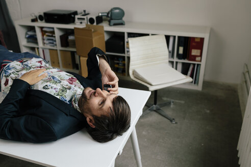 Casual businessman with cell phone lying on desk in office - BMF00876