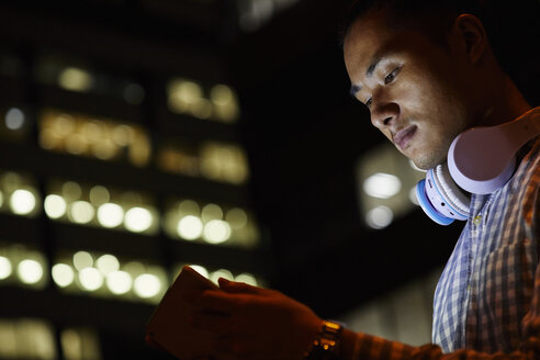 Portrait of young man in the city using tablet at night - JRFF01480