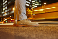 Feet of businessman standing at roadside in the city at night, close-up - JRFF01483