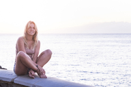 Portrait of smiling blond woman sitting on a wall in front of the sea - SIPF01853