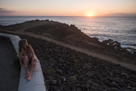 Spain, Tenerife, young woman sitting on a wall enjoying sunset near the sea - SIPF01859