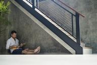 Mature man sitting under staircase, playing the ukulele - SBOF00870