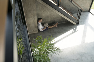 Mature man sitting under staircase, reading a book - SBOF00873
