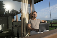Man sitting on balcony of modern house looking landscape, holding laptop - SBOF00876