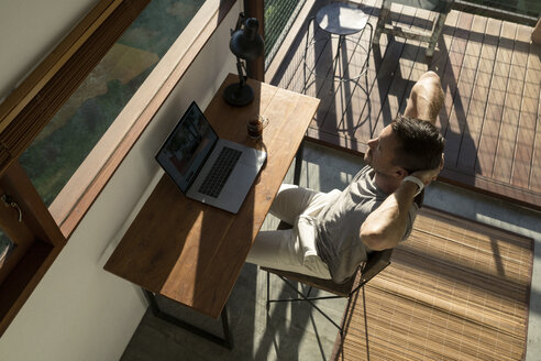 Man leaning back and taking a break from working at laptop on desk in house - SBOF00879
