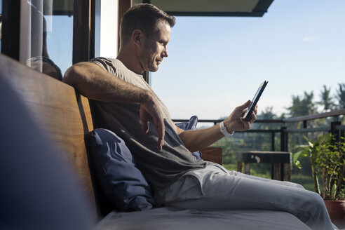 Man sitting on balcony of modern house, looking at smartphone - SBOF00882