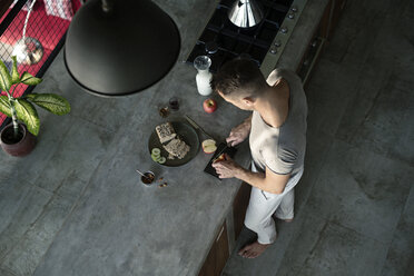 Mature man standing in kitchen, preparing healthy breakfast - SBOF00885