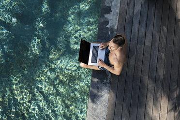Mature man sitting at the poolside, using laptop - SBOF00897