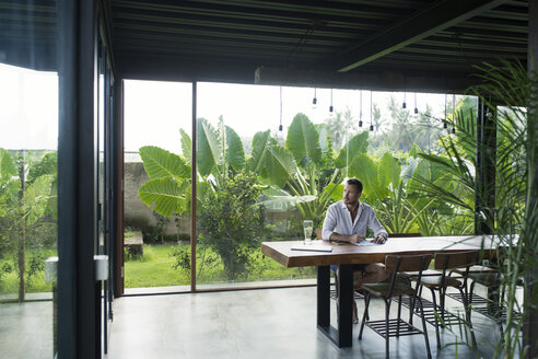 Mature man sitting at table in front of lush garden, writing - SBOF00906