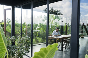 Mature man sitting at table in front of lush garden, writing - SBOF00909