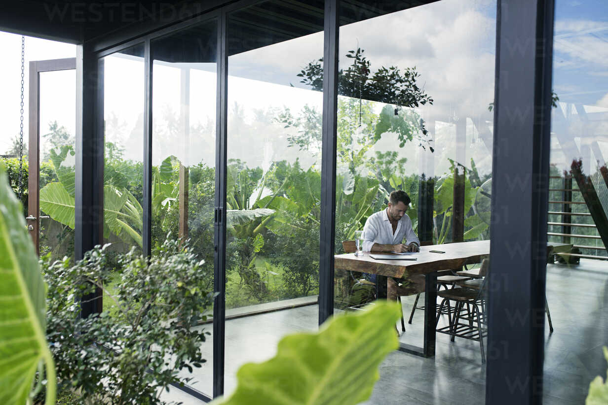 Mature man sitting at table in front of lush garden, writing - SBOF00909 - Steve Brookland/Westend61