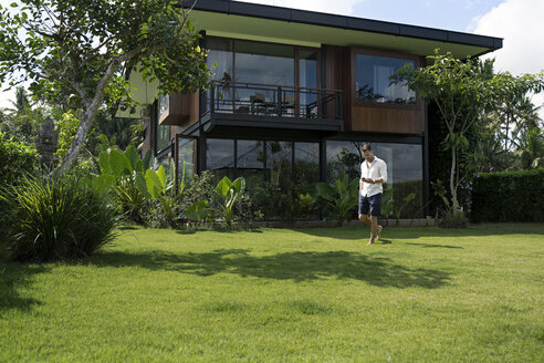 Mature man walking in garden in front of modern villa, using smartphone - SBOF00915