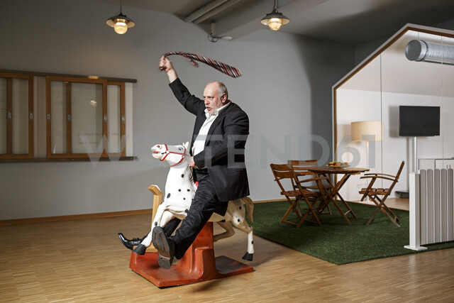 Businessman on rocking horse pretending to ride - PESF00750 - Peter Scholl/Westend61