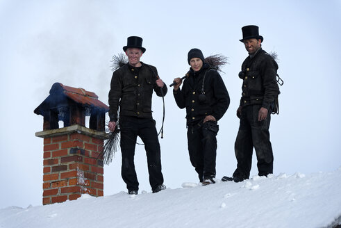 Group picture of three chimney sweeps standing on roof top - LBF01706