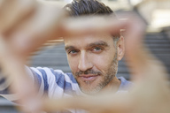 Portrait of mature man building frame with his fingers - PNEF00321