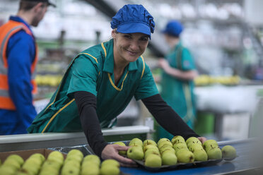 Portrait of smiling woman working in apple factory - ZEF14703