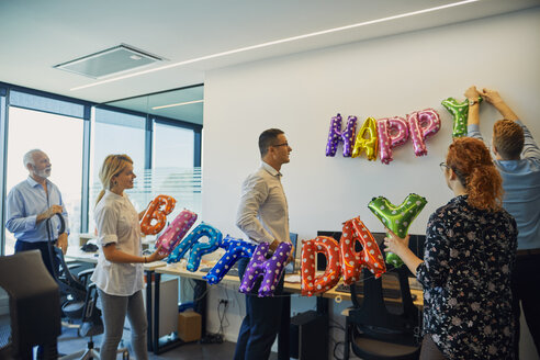 Colleagues decorating office with happy birthday writing - ZEDF00973
