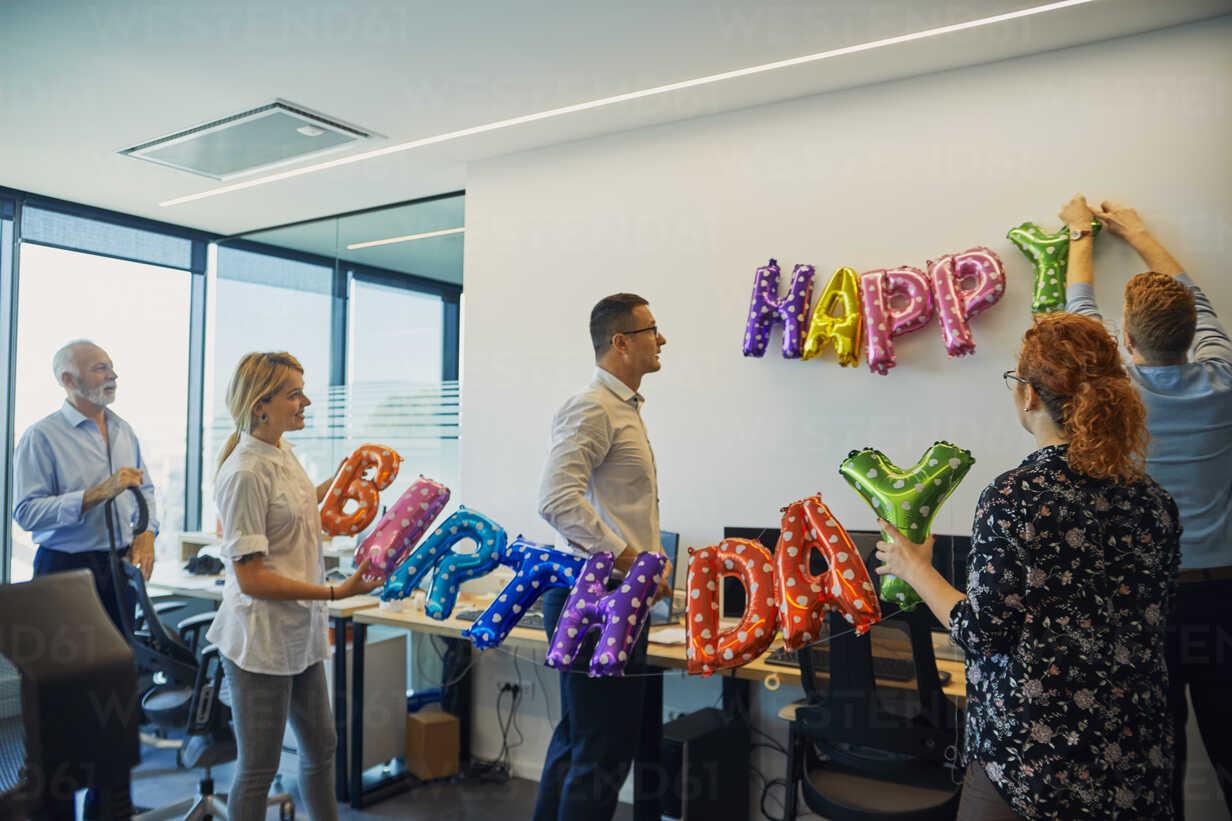 Colleagues decorating office with happy birthday writing - ZEDF00973 - Zeljko Dangubic/Westend61
