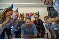 Colleagues having a birthday celebration in office with cake, party blower and party hats - ZEDF00976