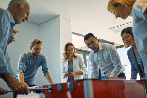Colleagues playing foosball in office - ZEDF00985