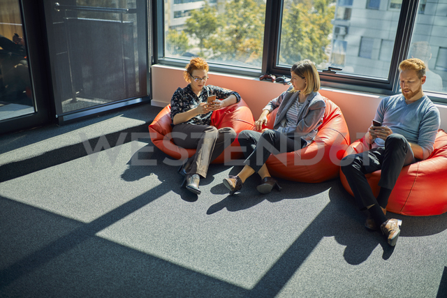 Colleagues with cell phones sitting in bean bags in office lounge - ZEDF00988