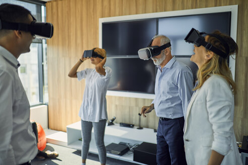 Colleagues wearing VR glasses in office - ZEDF00991