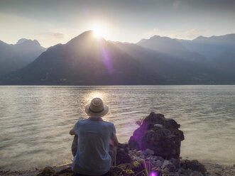 Italy, Lombardy, back view of man sitting at Lake Idro at sunset - LAF01947