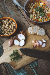 Mediterranean soup in copper pot, bowl of croutons and ingredients on wooden board - GIOF03291