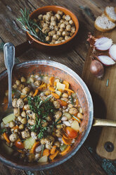 Mediterranean soup in copper pot, bowl of croutons and ingredients on wooden board - GIOF03294