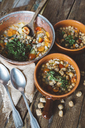 Mediterranean soup in copper pot and terracotta bowls on wood - GIOF03297