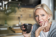Portrait of smiling senior woman with coffee mug in the kitchen - FMKF04625